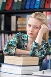 Fed Up Teenage Student In Library. Unhappy Teenage Student In Library Stock Photos