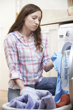 Fed Up Woman Doing Laundry a casa immagine stock