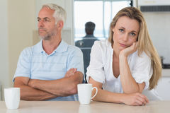 Fed up woman sitting at the counter with her partner. Fed up women sitting at the counter with her partner at home in the kitchen Stock Images