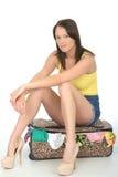 Fed Up Young Woman Sitting miserável furado em uma mala de viagem imagem de stock royalty free