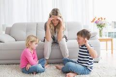Fed vers le haut de la mère écoutant ses enfants en bas âge combattent Photos libres de droits