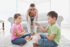 Fed vers le haut de la mère écoutant ses enfants en bas âge discutent Images stock