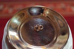 Fede nuziale classica dell'oro su un piatto di oro Immagine Stock