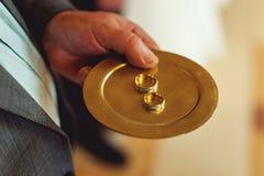 Fede nuziale classica dell'oro su un piatto di oro Immagini Stock
