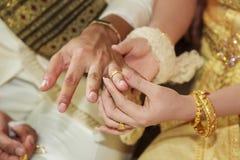Fede nuziale d'uso della sposa per la sua mano dello sposo Fotografie Stock Libere da Diritti