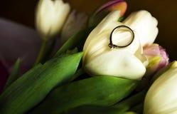 Fede nuziale disposta sui fiori fotografia stock libera da diritti
