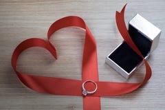 Fede nuziale e nastro rosso del cuore su superficie di legno fotografia stock libera da diritti