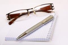 Feder auf dem Notizbuch, getrennt auf weißem Hintergrund. Lizenzfreies Stockfoto