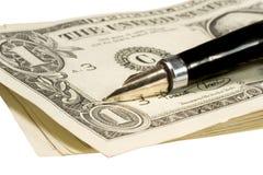 Feder auf Dollarscheinen Stockfotografie