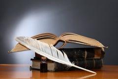 Feder auf dunklem Hintergrund gegen alte Bücher Lizenzfreies Stockbild