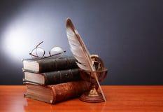 Feder auf dunklem Hintergrund gegen alte Bücher Stockbilder