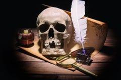 Feder auf dunklem Hintergrund gegen alte Bücher Alte Schreibtischgarnitur, Lupe, Schädel, Kerze und Spule auf alter Weinleserolle Stockbilder