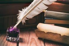 Feder auf dunklem Hintergrund gegen alte Bücher Alte Schreibtischgarnitur mit Feder nahe Rolle und Büchern Lizenzfreie Stockfotografie