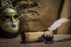Feder auf dunklem Hintergrund gegen alte Bücher Alte Schreibtischgarnitur mit Feder nahe Rolle und venezian Maske auf Segeltuchhi Stockbild