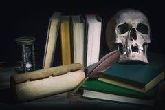 Feder auf dunklem Hintergrund gegen alte Bücher Alte Bücher mit dem Schädel nahe Rolle, Spulenfederstift und Weinlesesanduhr Lizenzfreie Stockfotografie