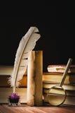 Feder auf dunklem Hintergrund gegen alte Bücher Schreibtischgarnitur mit Feder nahe Lupe und alter Rolle Stockfotografie