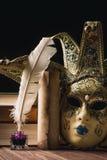 Feder auf dunklem Hintergrund gegen alte Bücher Schreibtischgarnitur mit Feder nahe venetianischer Maske, Büchern und alter Rolle Lizenzfreie Stockfotografie