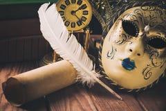 Feder auf dunklem Hintergrund gegen alte Bücher Stillleben mit Feder auf Rolle nahe venetianischer Maske, alte Bücher und Weinles Stockfoto