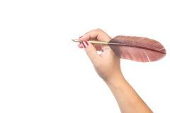 Feder auf dunklem Hintergrund gegen alte Bücher Weibliche Frauenhand mit roten Nägeln schreibt oder hält einen Federfederkiel lok Stockbilder
