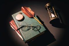 Feder auf dunklem Hintergrund gegen alte Bücher Weinlesestillleben mit Sanduhr nahe Gläsern auf alten Büchern nähern sich Feder o Stockfotos