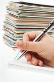 Feder in der Hand, die Postkarten schreibt. Stockbilder