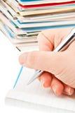 Feder in der Hand, die Postkarten schreibt. Lizenzfreie Stockbilder