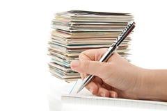 Feder in der Hand, die Postkarten schreibt. Stockfotos