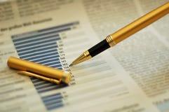 Feder, die Diagramm auf Finanzreport zeigt Stockbilder