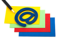Feder mit eMail-Symbol auf einem Stapel der Karten Stockbilder