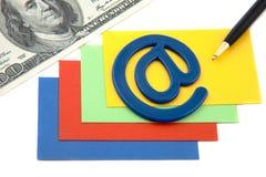 Feder mit eMail-Symbol und Bargeld auf einem Stapel der Karten Stockfotografie