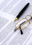 Feder und Brillen auf einer Dokumentennahaufnahme Lizenzfreies Stockbild