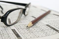 Feder und Gläser auf einem sudoku Spiel Lizenzfreies Stockfoto