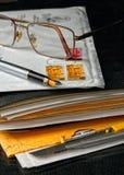 Feder und Gläser auf einem Umschlag Stockfoto