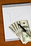 Feder und Notizblock mit Geld Stockfotografie
