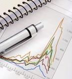 Feder und Notizbuch auf Diagramm Stockfoto