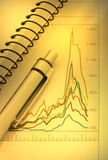 Feder und Notizbuch auf Diagramm Stockfotos