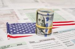 Federaal Inkomen 1040 belastingaangiftevorm met geld en vlag Stock Afbeelding