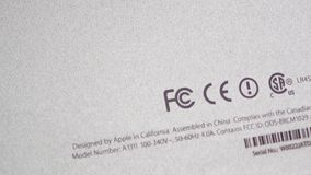 Federal Communications Commission logotype on computer back rear part. CALIFORNIA, UNITED STATES - CIRCA 2014: Pan to rear of Apple computers iMac with Federal stock video footage