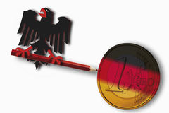 Federal eagle holding red pencil with german flag and euro coin on white background Stock Photo