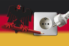 Federal eagle on red pencil with socket and plug against german flag Royalty Free Stock Photo