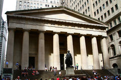 Federal Hall, New York City. Tourists at the facade of the Federal National Hall Memorial with its temple form with columns and the statue of George Washington royalty free stock image