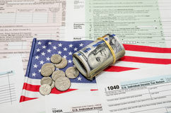 Federal Income 1040 tax return form with money and flag. US Federal Income 1040 tax return form with money and flag royalty free stock images