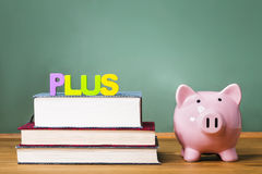 Federal PLUS Loan theme with textbooks and piggy bank Royalty Free Stock Photos
