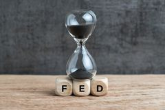 Federal Reserve, FED target and speed to raise interest rate con. Cept, hourglass or sandglass on cube wooden block with alphabet building acronym FED on wooden stock photography
