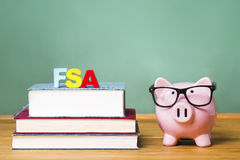 Federal Student Aid theme with pink piggy bank with chalkboard. In the background as concept image of the costs of education Stock Image