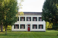 Federal-style Country Home. Large Federal-style house with red & green trim in the country surrounded with trees Stock Photography