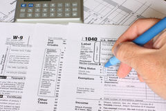 Federal Tax. A single man filling federal tax forms with a pen Stock Photos