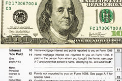Federal Tax Forms for Items Deductions. One hundred dollar bills sitting on tax papers, Federal Tax Forms for Items Deductions Stock Photo