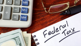 Federal tax. Federal tax written in a notebook and calculator Royalty Free Stock Photos