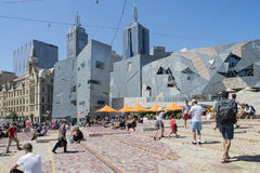 Federation Square, Melbourne, Australia. Tourists and locals alike relax under umbrellas and on the steps in Federation Square, Melbourne, Australia stock photos
